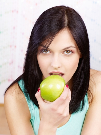 Pretty woman eating green apple