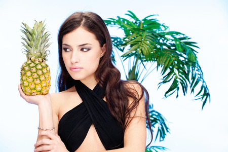 Pretty dark hair woman holding pineapple in front of a palm tree
