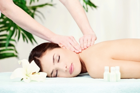 Brunette woman on neck massage in spa center Stock Photo