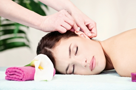 Pretty woman on ear massage in salon photo