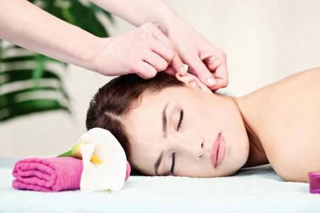 Pretty woman on ear massage in salon