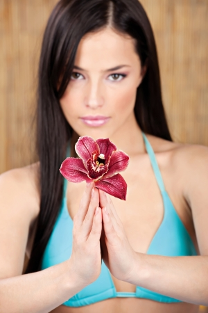 Red orchid in hands of a pretty woman in bikini, focus on flower