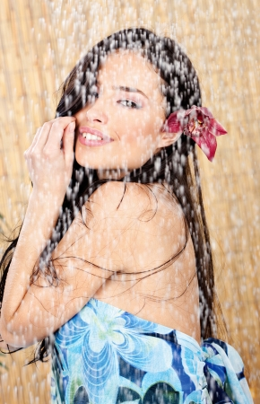young woman with orchid in her hair having a shower