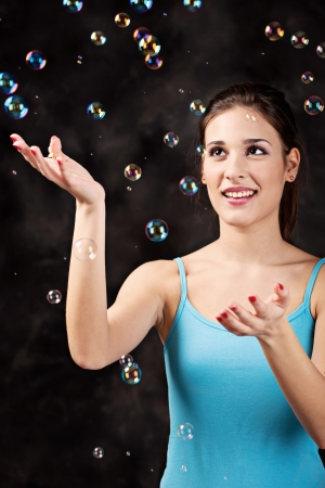 Pretty girl and soap bubbles on the black background