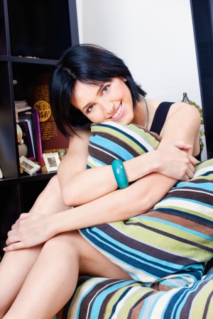 Cute black hair woman behind pillow at home