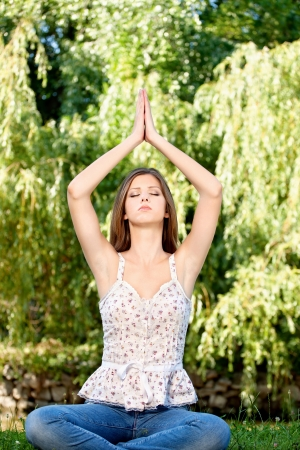 Young woman in lotus pose at the meditation outdoor