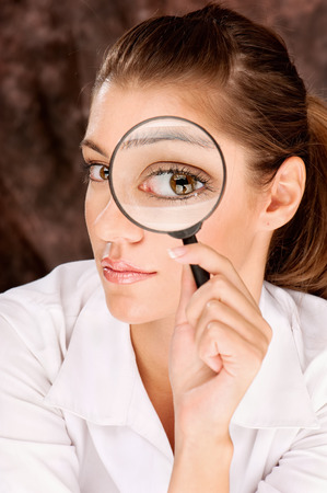 Pretty female researcher looking through magnifier glass Stock Photo