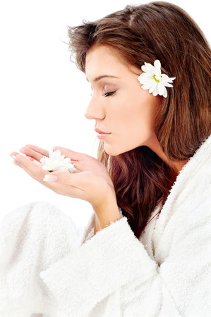 Pretty woman in bathrobe  smelling flower, isolated on white