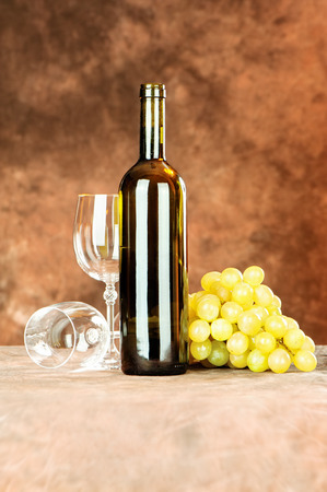 Wine bottle and shiny wine cup near grape Stock Photo