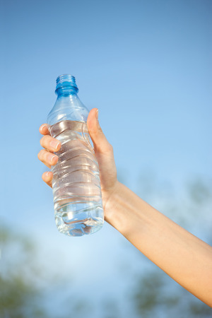 hand holding plastic bottle of water in front of sky