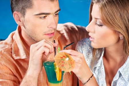 young couple outdoor drinking cocktail on summer evening