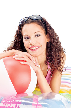 Pretty curl girl with sun glasses in hair, laying air mattress and holding the ball, isolated on white Stock Photo