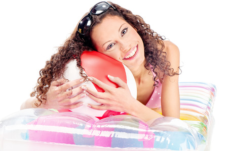 Smiled curl girl with sun glasses in hair, laying air mattress and holding the ball, isolated on white