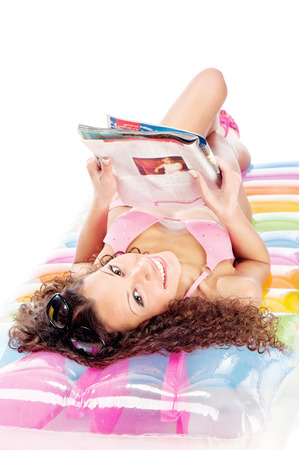 Pretty curl girl reading newspaper on air mattress, isolated on white