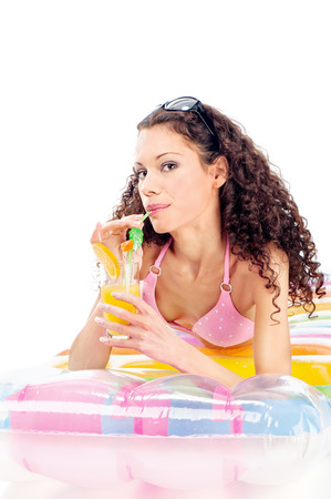 Pretty curl girl drink juice on air mattress, isolated on white