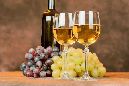 cups of white wine in front of grape and bottle