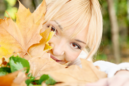 young blonde behind the leaves on summer day