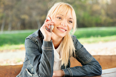 Blond woman at park taking a phone call Stock Photo
