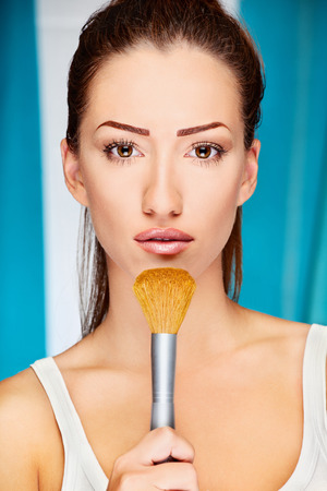 Portrait of a pretty young woman holding powder brush