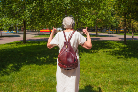 The back view of senior gray woman with earphones showing thumbs up in the park Stockfoto