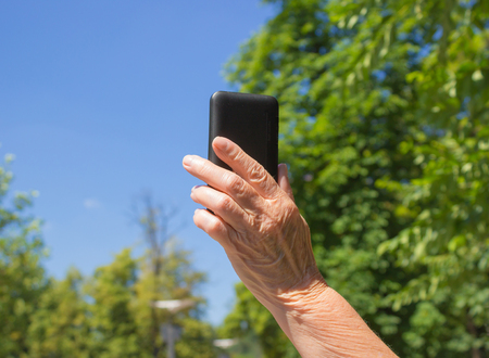 eldest: The phone in old female hand on the blue sky background