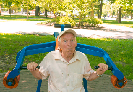 going in: The surprised old man going in for sports on a street simulator in park
