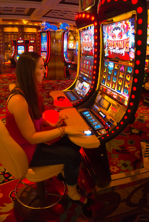 machines: LAS VEGAS - MAY 06, 2016: Concentrated girl playing slot machines in the Excalibur Hotel and Casino