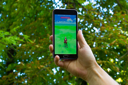 real world: Dnipro, Ukraine - July 23, 2016: The hit augmented reality smartphone app Pokemon GO shows a Pokemon encounter overlain in park in the real world.