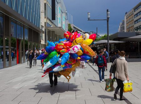 walking zone: Frankfurt, Germany - June 15, 2016: The dealer of colorful balloons walking along the Zeil in Midday in Frankfurt, Germany. Since the 19th century it is of the most famous and busiest shopping streets in Germany.