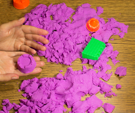 motility: The female hands with pink kinetic sand