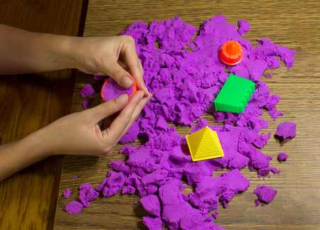 kinetic: The female hands with pink kinetic sand