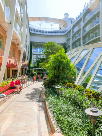 allure: Barselona, Spaine - September 06, 2015: Royal Caribbean, Allure of the Seas sailing from Barselona on September 6 2015. The second largest passenger ship constructed behind sister ship Oasis of the Seas. Passengers sitting at Central Park