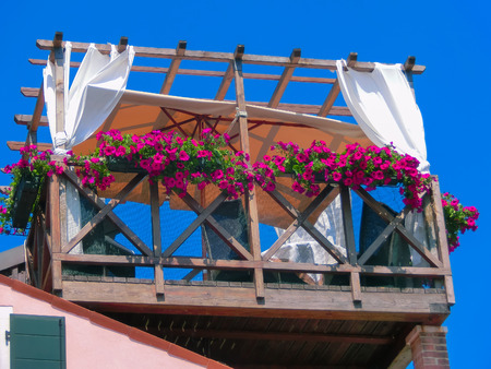 tourist site: Burano, Italy - May 10, 2014: The original wooden veranda with table and chairs in Burano island near Venice. The island is a populat tourist site Editorial