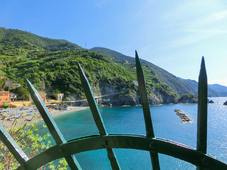 monterosso: The coastline of Monterosso in Italy through the iron bars. Monterosso is one of five famous coastline villages in the Cinque Terre National Park.