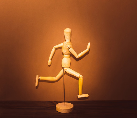 artists dummy: The figure of wooden man, running on wooden background Stock Photo