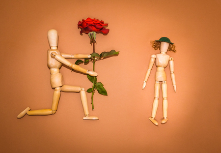 flower petal: Red rose and figure wooden man and woman on brown background Stock Photo