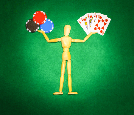 jack pot: The wooden man with hands up to hold chips and cards for playing poker