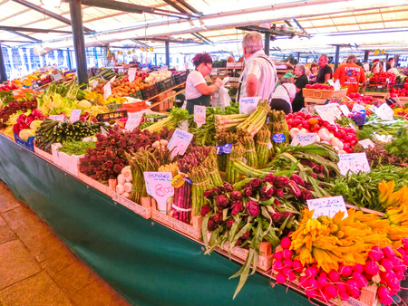 the merchant of venice: Venice, Italy - May 10, 2014: People near a counter with vegetables on a market in Venice, Italy