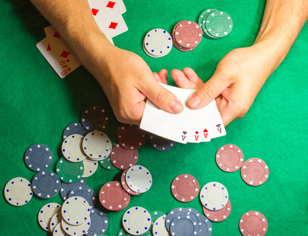 The male hands with cards in casino and chips