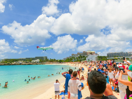 juliana: Philipsburg, Sint Maarten, Netherlands - May 14, 2016: The beach at Maho Bay is one of the worlds premier planespotting destinations. Airplanes landing at the Princess Juliana Airport fly over beachgoers.