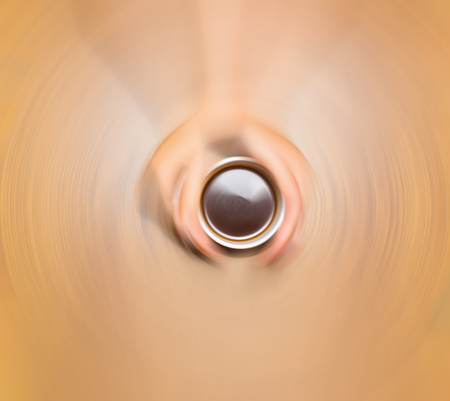 postproduction: Female hands holding cup of coffee on wooden background, blurred in postproduction