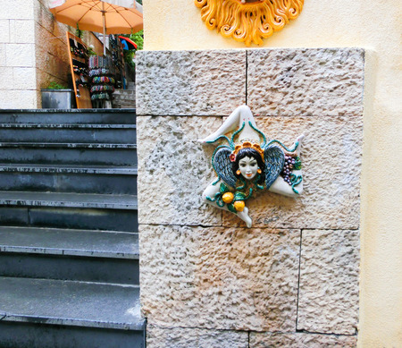 characteristic: Triskelion - motif used in the flag of Taormina, found on one of the walls, Sicily island, Italy Stock Photo