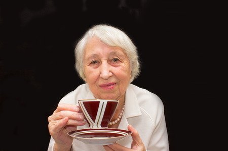 residental care: The Senior Woman Enjoying Cup Of Tea on black