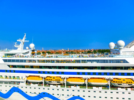 docked: Venice, Italy - June 06, 2015: Cruise liner AIDA Vita docked at the port of Venice, Italy on a background of the roofs on June 06, 2015