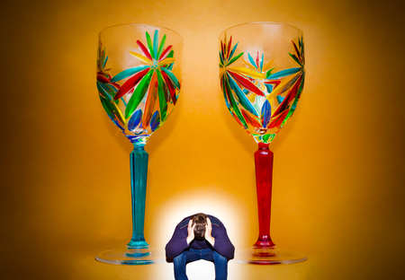 Portrait of two wineglasses and depressed man. Concept of youth addicted to alcohol, alcoholism, social problem