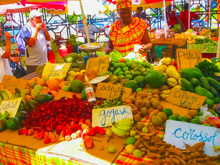 Point-a-Pitre, Guadeloupe - February 09, 2013: woman sells fresh fruits at the outdoor market in Guadeloupe.