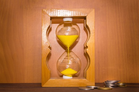 The glossy old-style hourglass standing with a coins