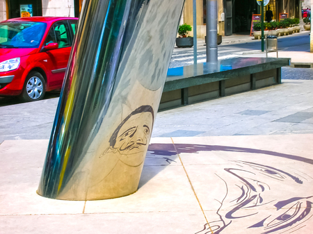 Figueres, Spain - May 07, 2007: The unclear image on the ground is reflected on to the cylindrical pillar to form the image of the Salvador Dali with his famous moustache