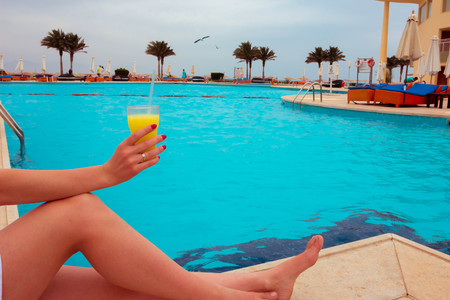 The woman enjoying cocktail in a swimming pool