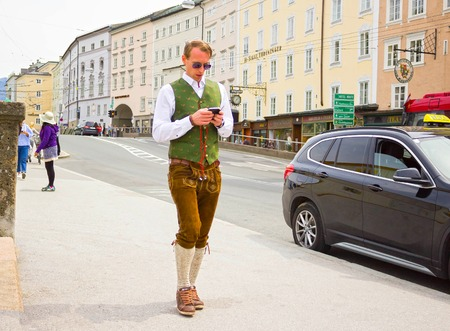 Salzburg, Austria - May 01, 2017: Men wearing traditional Austrian costume going with mobile phone at street on sunny day